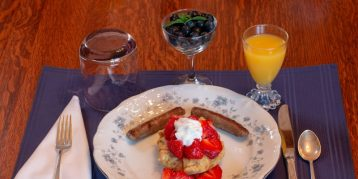 Close up of a breakfast plate with strawberries on top of a pancake, orange juice, blueberries, and fine silverware