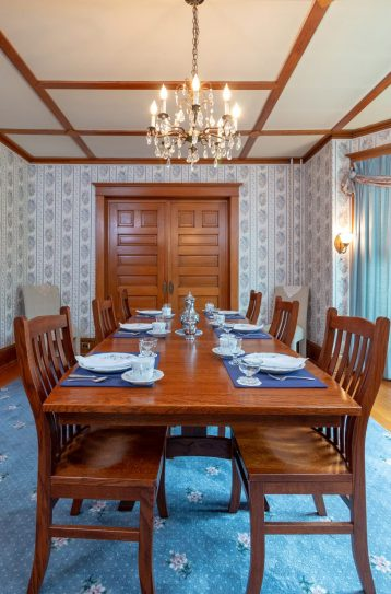 The dining table is set evenly on top of light blue carpet