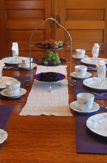 The table is set with fine china and blue placemats