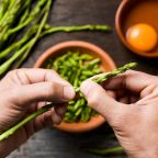 Hands preparing asparagus for a frittata