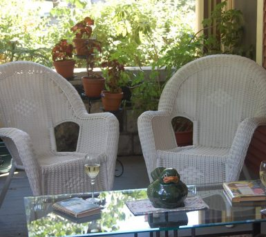 Two chairs next to each other on the porch ready to be sat in and enjoyed by two friends company