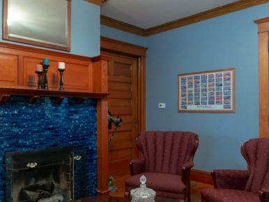 The main parlor has a fireplace and two red chairs with fine crystal on the table