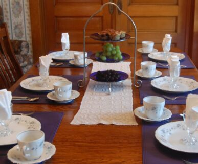The table is set with fine china and tea cups