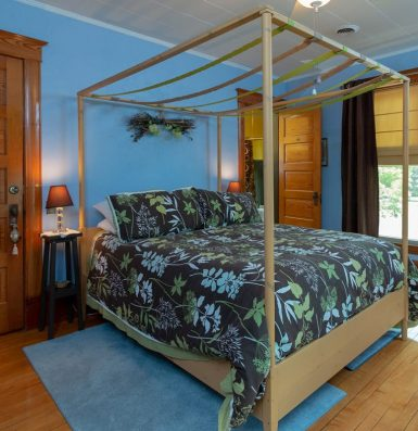 A room painted blue with a modern floral bedsheet a top the bed