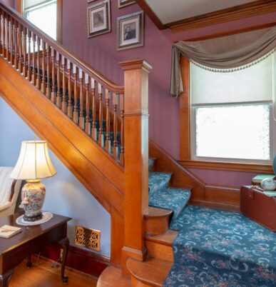 A view of the stairway with blue carpet lining the antique wood floors