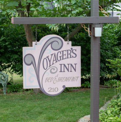 The wooden Voyager's Inn sign hangs with pride in the front lawn
